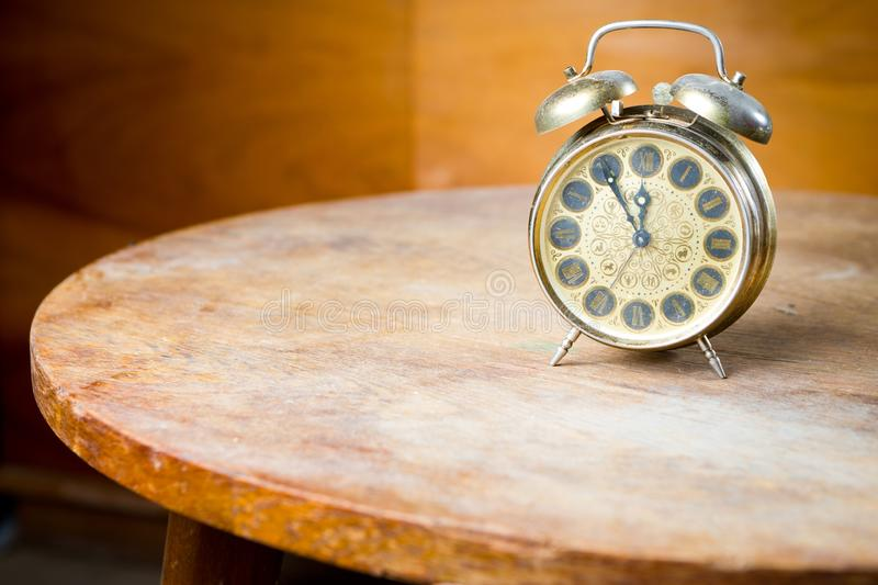 Old used alarm clock on rounded table. Obsolete technology but great design - Five to twelve stock image