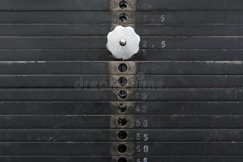 Old and used black weight stack with white numbers in a gym. Rusty flat metal weights. stock photography