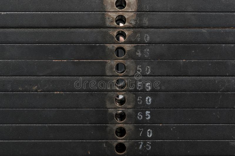 Old and used black weight stack with white numbers in a gym. Rusty flat metal weights. royalty free stock photo