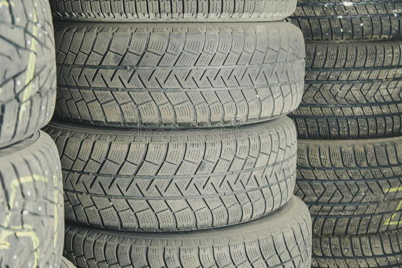 Old and used car tires. Background. Car tires in storage. Car tire recycling stock image