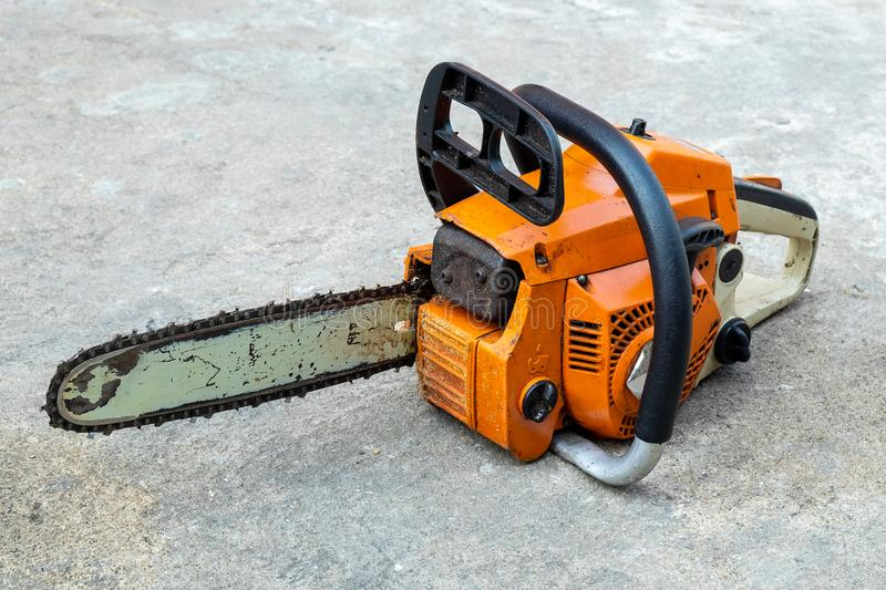 The Old and Used Chainsaw Machine on the Concrete Floor royalty free stock photos