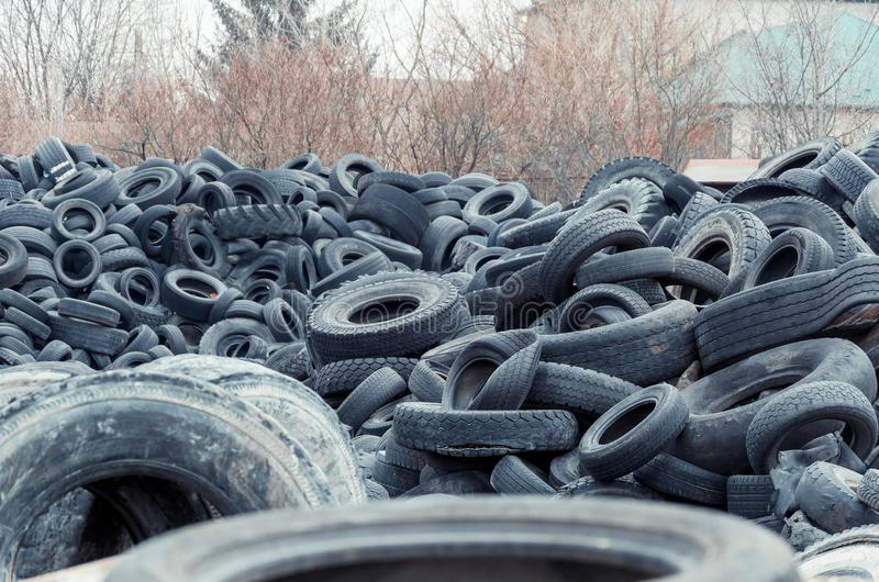 Old used damaged car tires at the dump royalty free stock photography