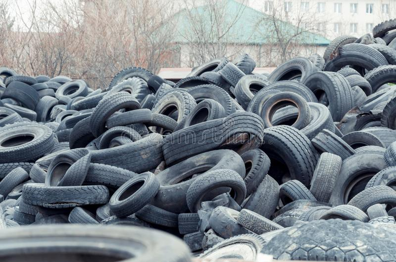 Old used damaged car tires at the dump stock photo