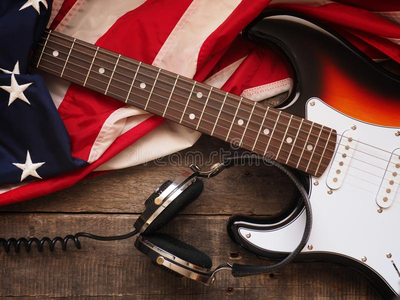 Old used guitar with headphones and American flag. Old used rock guitar with headphones and the American flag on rustic wood, music or sound concept background stock photos