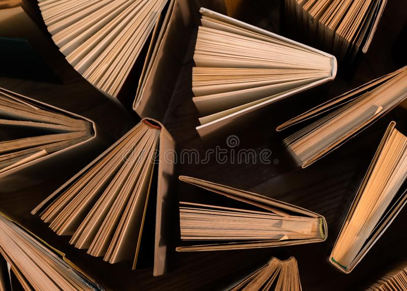 Old and used hardback books, text books seen from above on wooden floor. Books and reading are essential for self improvement, ga. Ining knowledge and success in royalty free stock photos