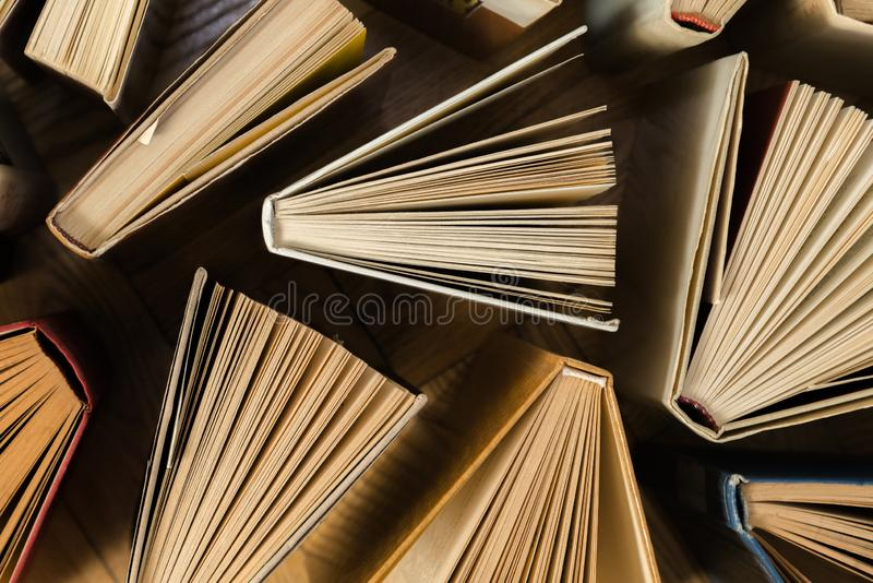 Old and used hardback books, text books seen from above on wooden floor. Books and reading are essential for self improvement, ga. Ining knowledge and success in royalty free stock photography
