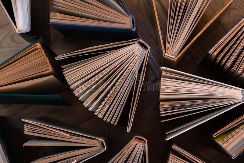 Old and used hardback books, text books seen from above on wooden floor. Books and reading are essential for self improvement, ga. Ining knowledge and success in royalty free stock photo