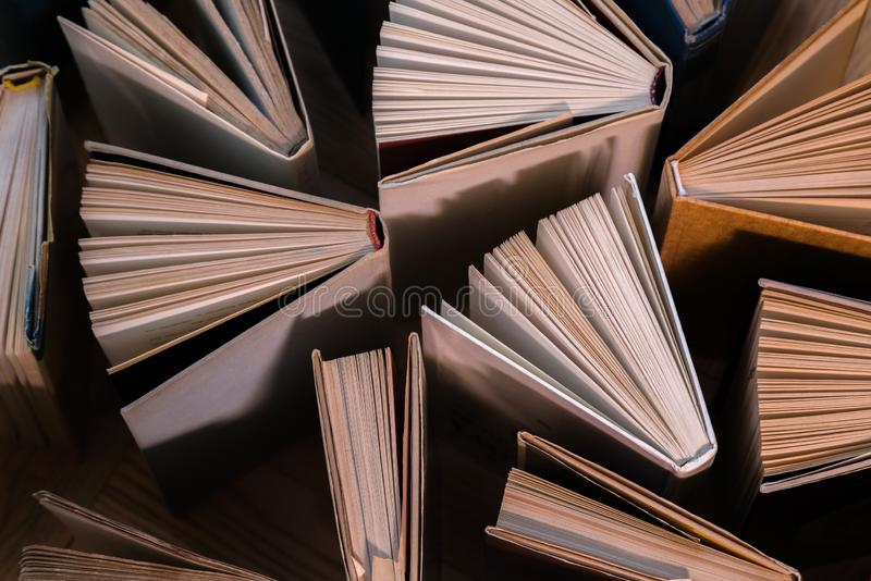 Old and used hardback books, text books seen from above on wooden floor. Books and reading are essential for self improvement, ga. Ining knowledge and success in stock photo