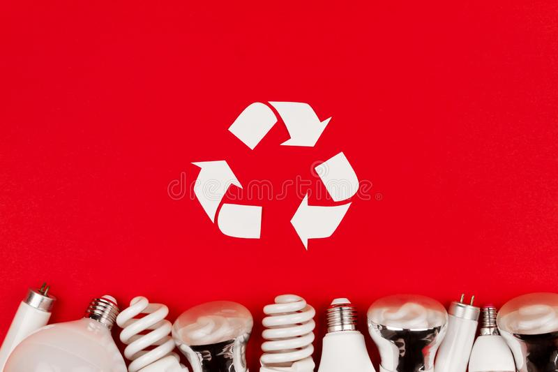 Reuse recycling sign symbol environment light bulbs concept. Old used metal led, incandescent halogen cfi fluorescent, lumens light bulbs tube on red background stock photos