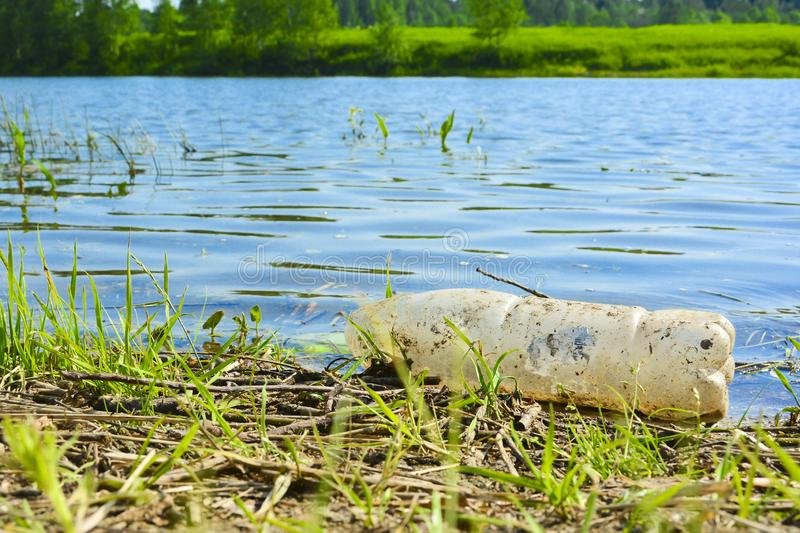 Old used plastic bottles on the river. Polluted bank of the river. Plastic bottles and trash in water. Environmental destruction stock images