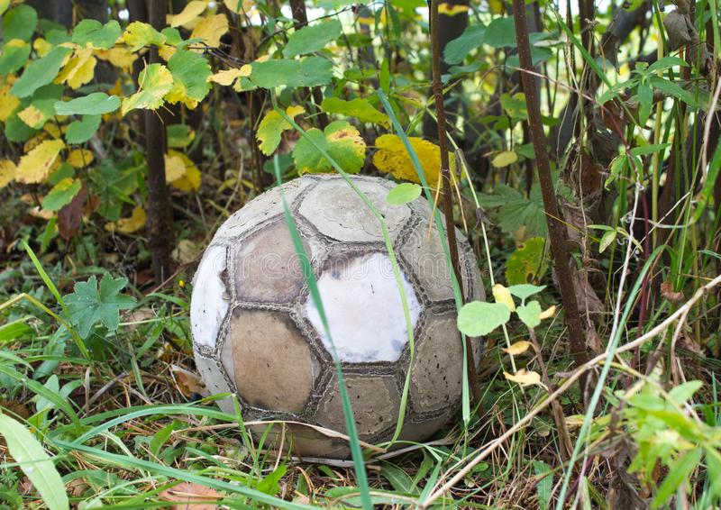 Old used soccer ball in the grass on the ground stock photo