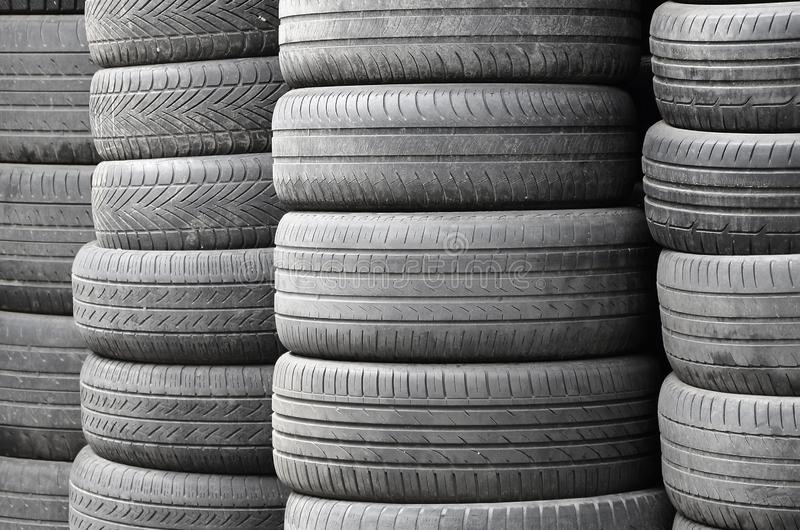 Old used tires stacked with high piles in secondary car parts shop garage royalty free stock images