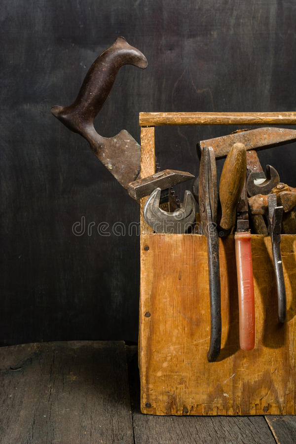 Old used tools in the toolbox. Dark background. spot lighting. Wooden box. Repair work royalty free stock photo
