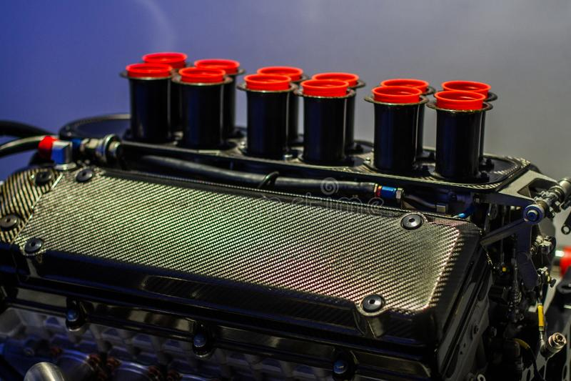 Old v12 formula 1 sport engine with carbon fiber valve cover. And red throttle pipes stock image