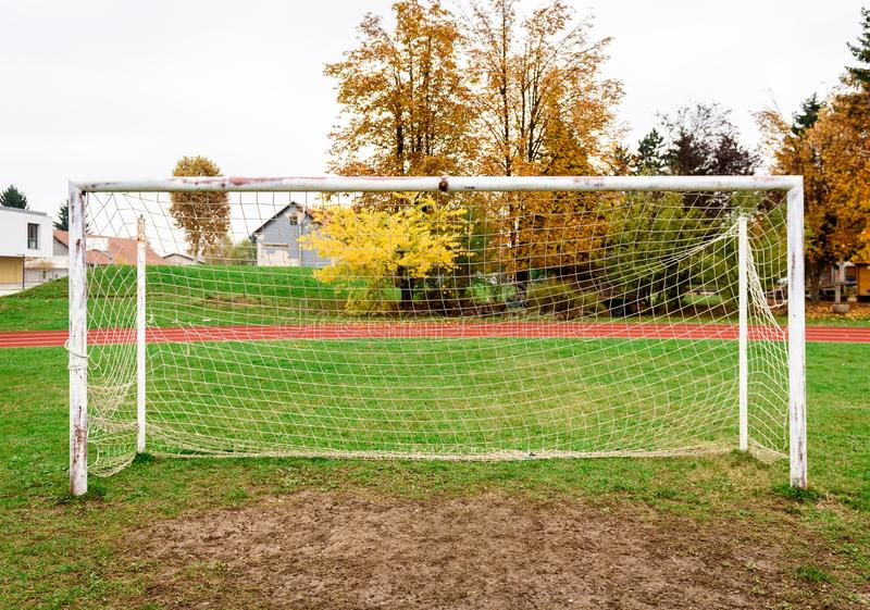 Old vacant football soccer goal gate in rural grass field. Old sports field with rusty goal and net on meadow with muddy front line stock photos