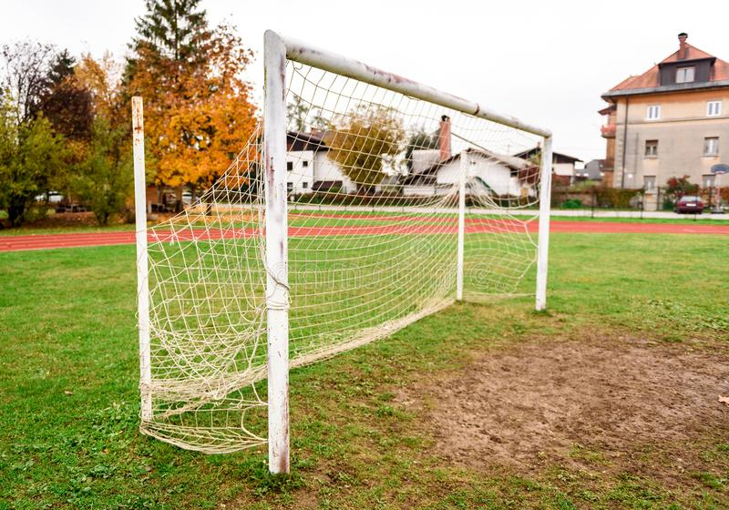 Old vacant football soccer goal gate in rural grass field. Old sports field with rusty goal and net on meadow with muddy front line royalty free stock photos