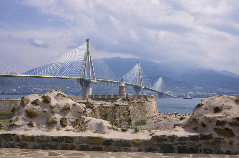 Old versus new, aged lighthouse versus modern cable bridge royalty free stock photography