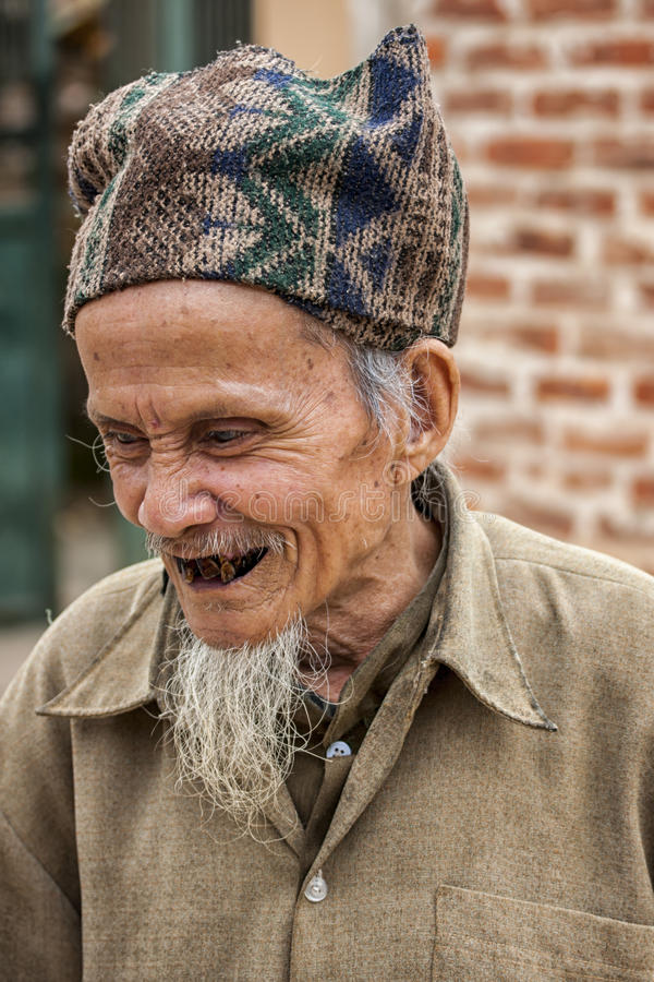 Old Vietnamese man with extremely bad teeth. HANOI, VIETNAM - MARCH 8, 2012: An old man, claiming to be in his eighties and a French teacher has extremely bad stock images