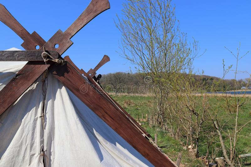 Old vikings tent made of cloth and wood in front of a blue sky stock photography