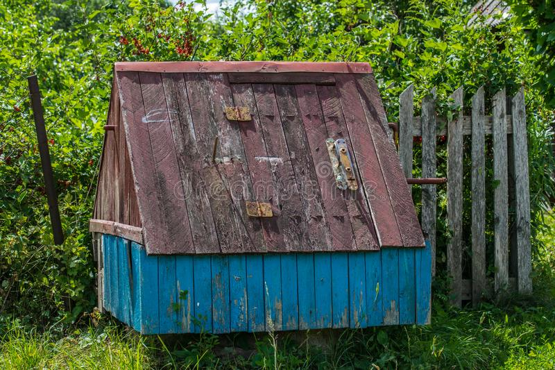 Old wooden well with a house in the countryside. Old village well against the background of an overgrown garden. Old village well against the background of an stock images