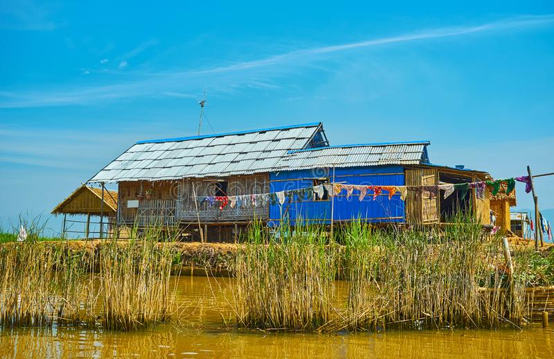 The house of villagers on Inle Lake, Myanmar. The old villagers` house with drying clothes behind the thicket of reeds on Inle Lake, Ywama, Myanmar royalty free stock photo