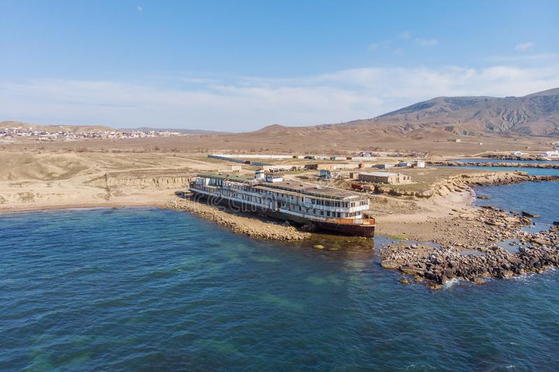 Old vintage abandoned rusted ship run aground after shipwreck accident in beginning of XX century in Crimean coast. On sand beach, aerial view from drone royalty free stock image