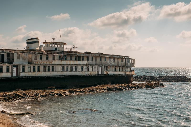 Old vintage abandoned rusted ship run aground after shipwreck accident in beginning of XX century in Crimean coast on sand beach. Toned royalty free stock images