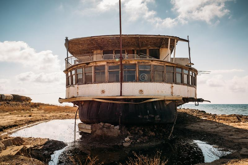 Old vintage abandoned rusted ship run aground after shipwreck accident in beginning of XX century in Crimean coast on sand beach. Toned stock photos