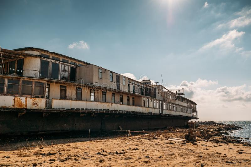 Old vintage abandoned rusted ship run aground after shipwreck accident in beginning of XX century in Crimean coast on sand beach. Toned royalty free stock photo