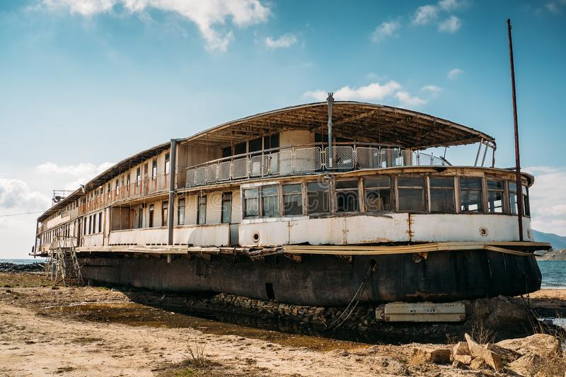 Old vintage abandoned rusted ship run aground after shipwreck accident in beginning of XX century in Crimean coast on sand beach. Toned royalty free stock photos