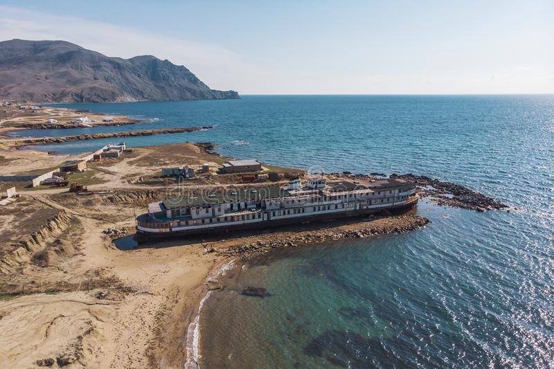 Old vintage abandoned rusted ship run aground after shipwreck long time ago sea coast on sand beach, aerial view. From drone royalty free stock photography