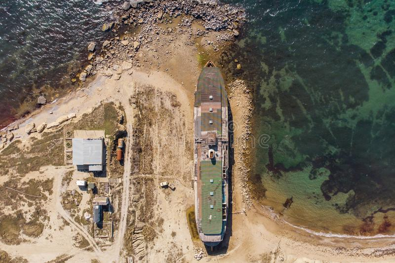 Old vintage abandoned rusted ship run aground after shipwreck long time ago sea coast on sand beach, aerial view. From drone royalty free stock image