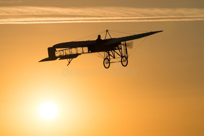 Old vintage airplane flying in an orange sky at sunset royalty free stock photo