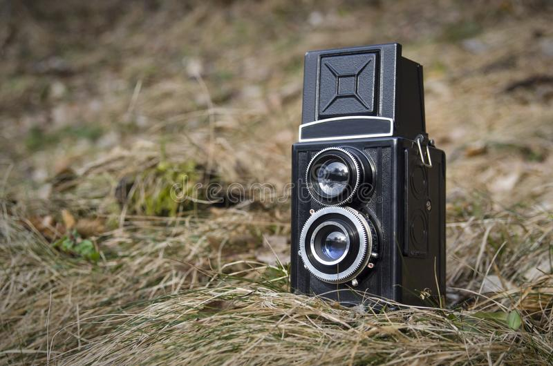 Old vintage analog photo camera in nature grass background stock image