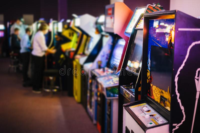 Old Vintage Arcade Games in a dark room and players playing in the background stock image