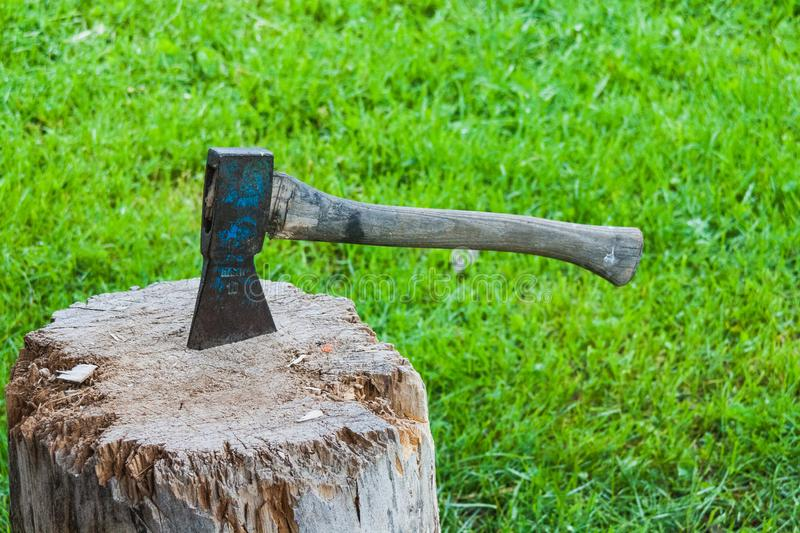 Old vintage axe is stuck in a piece of log wood stock images