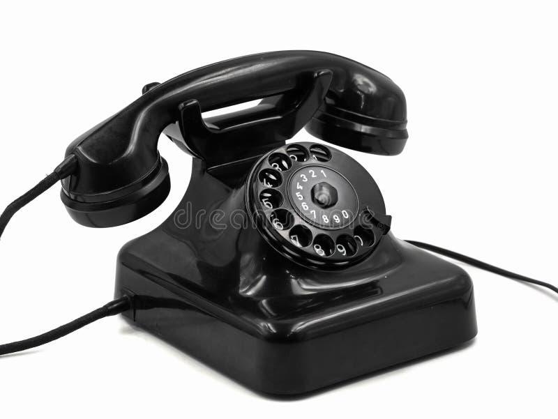 Old vintage black rotary dial telephone isolated on white background, retro bakelite phone.  stock image