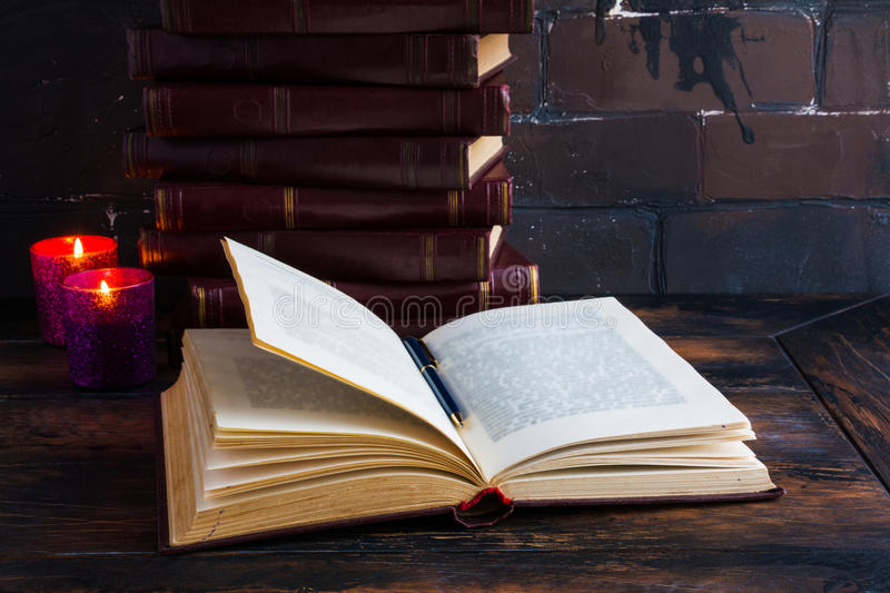 Old vintage books laying like a tower on a dark wooden table and one open book. Red hard cover, burning candle flames stock photo