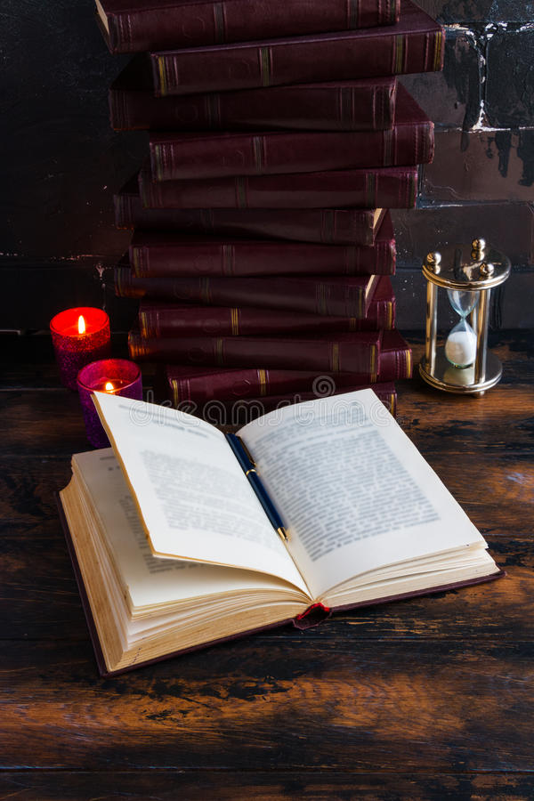 Old vintage books with red hard cover laying like a tower on a dark wooden table and one open book. royalty free stock photos
