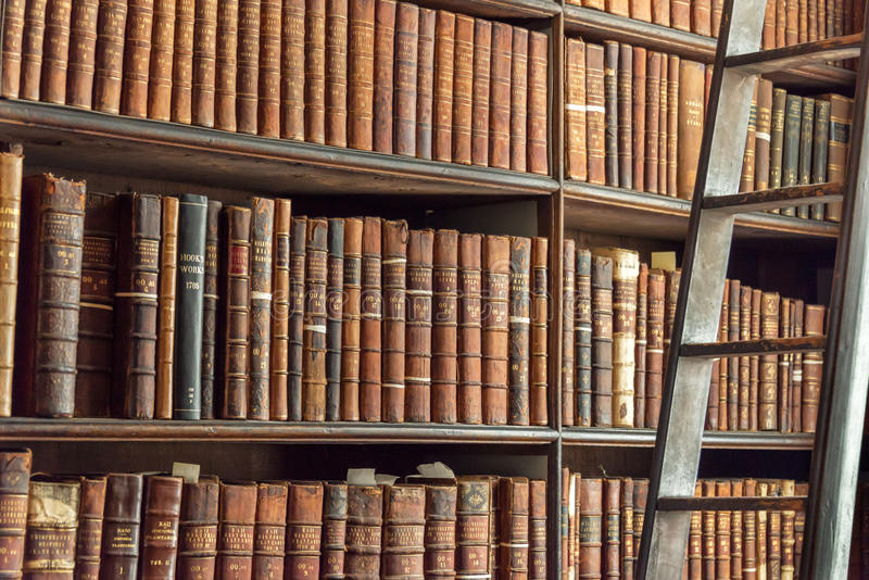 Old vintage books on wood bookshelf and ladder in a library stock images