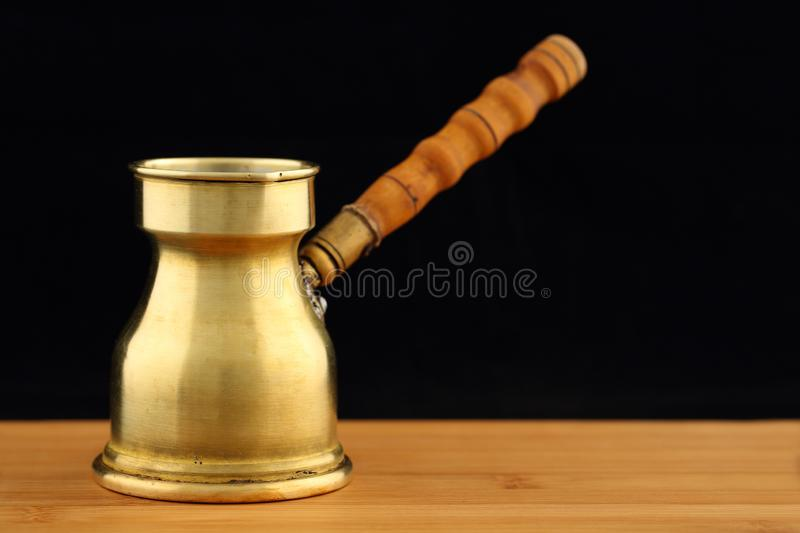Old, vintage brass turkish coffee pot dzhezve with carved wooden handle on a wooden table against black background royalty free stock photography