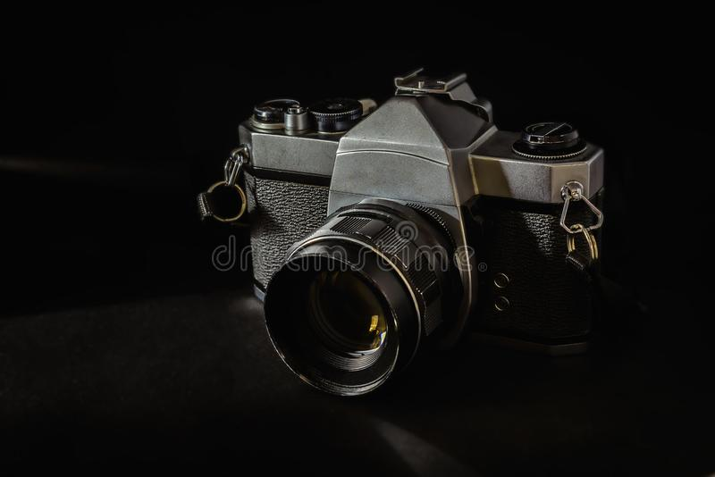 Old vintage camera that has been used for a long time on a black background.  stock image
