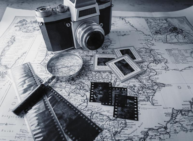 Old vintage camera on map with negatives stock photography