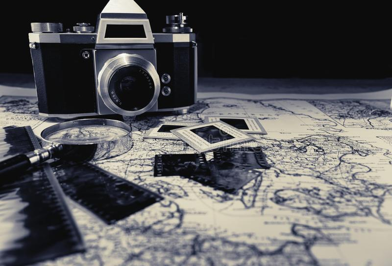 Old vintage camera on map with negatives. Old pictures and a magnifier glass. Retro, nostalgic, photography concepts stock images