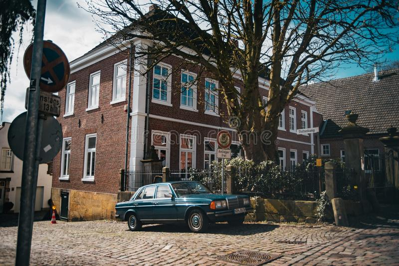 Old vintage car on german cozy street. With red brick houses royalty free stock images