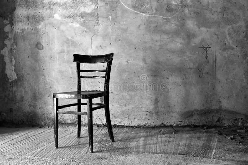 Old vintage chair. Vintage old black wooden chair in grungy interior. Loneliness, estrangement, alienation concept royalty free stock photo