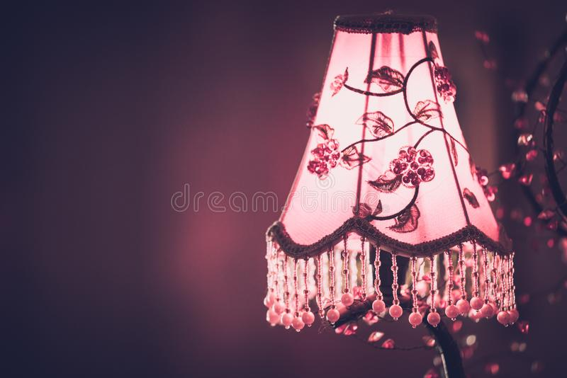 Old vintage chandelier with colorful textile cover on the wall with copyspace. In warm toning background decor design decoration glass lamp light retro style stock photo