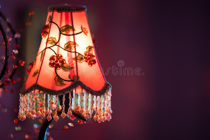 Old vintage chandelier with colorful textile cover on the wall with copyspace. In warm toning background decor design decoration glass lamp light retro style stock images
