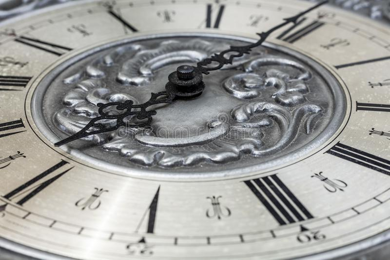 Old vintage clock with metal dial and floral embossed pattern close-up. Black clock hands indicating a time of 6 hours. Beautiful royalty free stock image