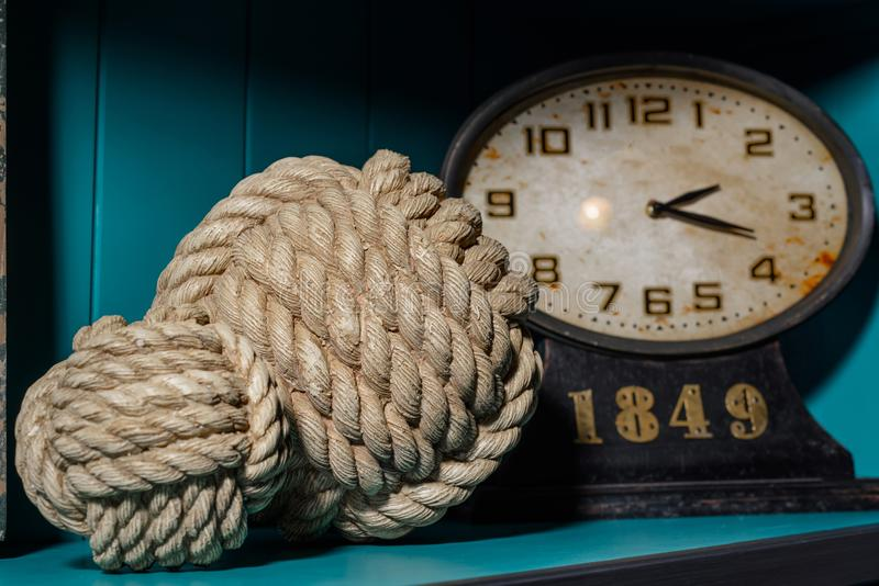 Old vintage clock and two different thread balls on wooden shelf. In room stock image